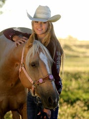 Clay Barry, a freshman rodeo athlete for New Mexico State University, poses with her horse.