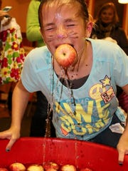 Grace Arndt bobs for apples during a previous Pumpkin