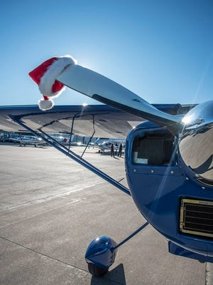 A Santa Claus hat dots the wing of a plane before takeoff at Centennial Airport as part of the Charity Airlift on Sunday, Dec. 10, 2017.