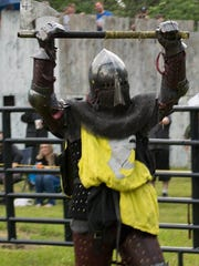 "Sean Krachun celebrates a win in a fight in a tournament. He holds up an axe. Krachun is a ""medieval fighter"" in the Armored Combat League, an international league started in the U.S., which has more than 400 fighters."