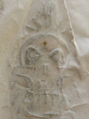 Reverse side of the hand drawn picture of a skull glued