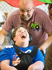 Jacob Wilson, 14, laughs as he gets a push by his buddy