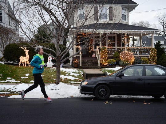 A runner jogging Sunday on the streets in Rutherford to avoid ice and slush left by a winter storm earlier in the weekend. Despite an unseasonably warm start to the day, temperatures dove back into the 40s by early afternoon.