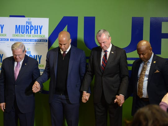 From left, Sens. Bob Menendez and Cory Booker, Murphy and Newark Mayor Ras Baraka in prayer at the news conference on Monday.