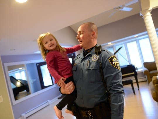 Wayne Police Officer Brian Hackett plays with Nicole