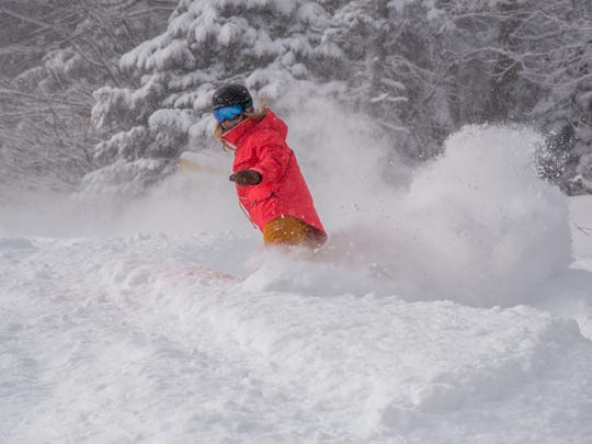 A Stratton snowboarder enjoys knee-deep powder after Sunday's storm dumped 15 inches of snow.