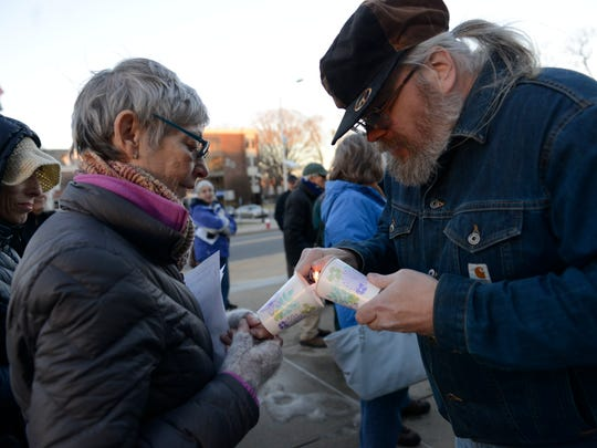 """Bob Weiss of Teaneck helps Mimi Donson of Teaneck light a candle during the """"New Birth of Freedom"""" vigil on Feb. 20, 2017 in Hackensack."""