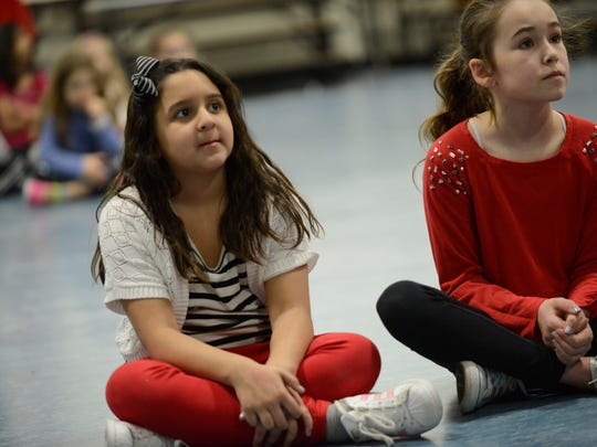 """Third graders Cadence Mendoza and Julia Whaley listen to the reading of """"Green Eggs and Ham"""" during Norwood Public School's kick off to Read Across America on March 2, 2017."""
