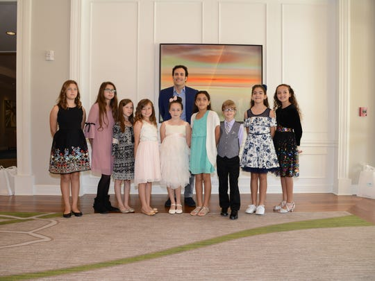 The nine winners of the Barbara Bush Foundation for Family Literacy's student essay contest pose for a photo with Jeb Bush Jr.