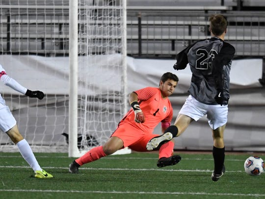 Castle's goalie Michael Bertram (1) moves to protect the goal against Harrison's Jakub Hall (23) in the Class 3A state championship match at Michael A. Carroll Stadium in Indianapolis.