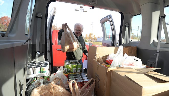 Doug Versaw loads food donations into a van Friday morning during the Make a Difference Day Food drive.