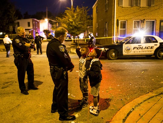 Two boys talk with a Wilmington police officer near