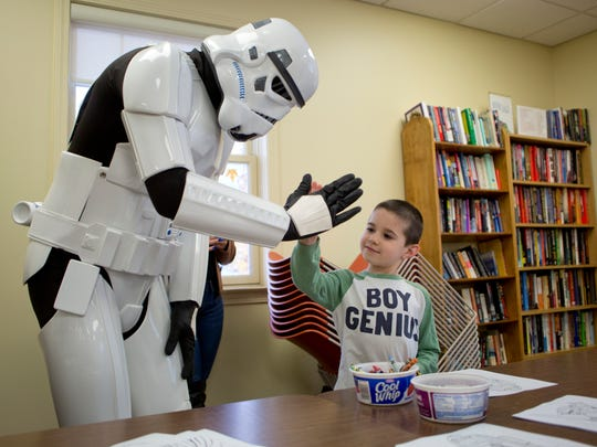 Kameryn Servick, 6, of Marine City, claps hands with a Storm Trooper during a meet-and-greet with Star Wars characters Saturday, November 21, 2015 at the Marine City Public Library.
