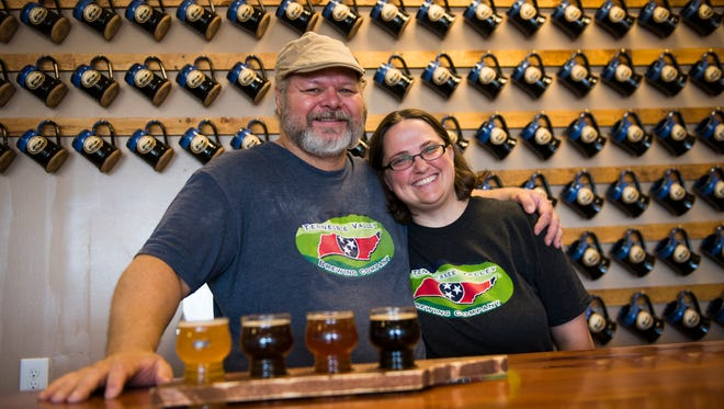 """Eric and Wendy Brannstrom, owners of Tennessee Valley Brewing Company, pose for a portrait along their wall of mugs for their currently 100-member """"Mug Club."""""""