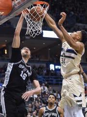 Spurs center Pau Gasol (16) dunks against Bucks forward Giannis Antetokounmpo.