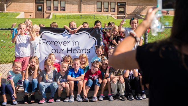 Students at Fiddlers Canyon Elementary gather around the poster they hung on the first day of school Tuesday in remembrance of teacher Merilee Jones.