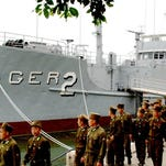 FILE - In this Thursday, June 22, 2006 photo released by North Korea's Korea Central News Agency via Korea News Service, North Korean soldiers watch USS Pueblo, which was seized by North Korean navy off the Korean coast in Jan. 1968, near Taedonggang river in Pyongyang. The ship is North Korea's greatest Cold War prize, a potent symbol of how the country has stood up to the great power of the United States, once in an all-out ground war and now with its push to develop the nuclear weapons and sophisticated missiles it needs to threaten the U.S. mainland. (AP Photo/Korea Central News Agency via Korea News Service)