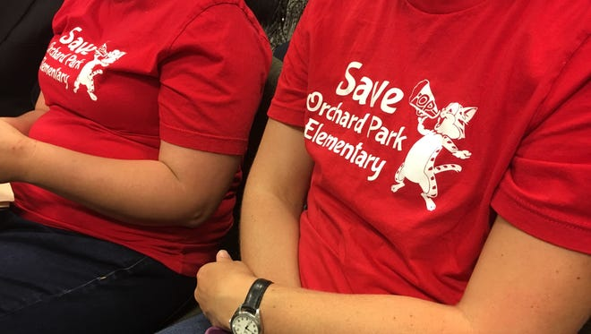 "Parents wearing ""Save Orchard Park Elementary"" shirts sit in the crowd during the May 21 Carmel school board meeting."