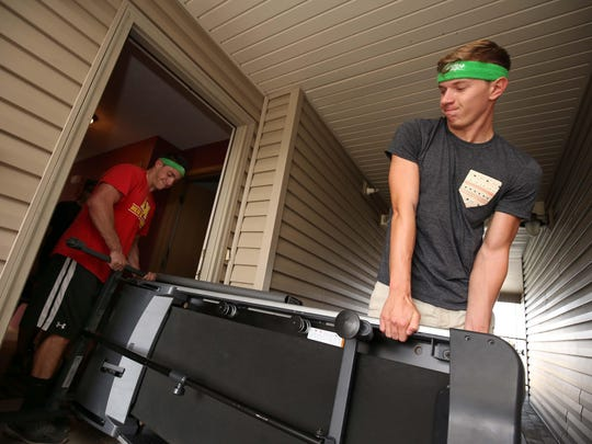 Bellhops' Jade Pavia, left, and Allen Bates move an extremely heavy treadmill.