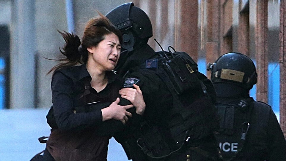 A hostage runs to police officers after escaping an