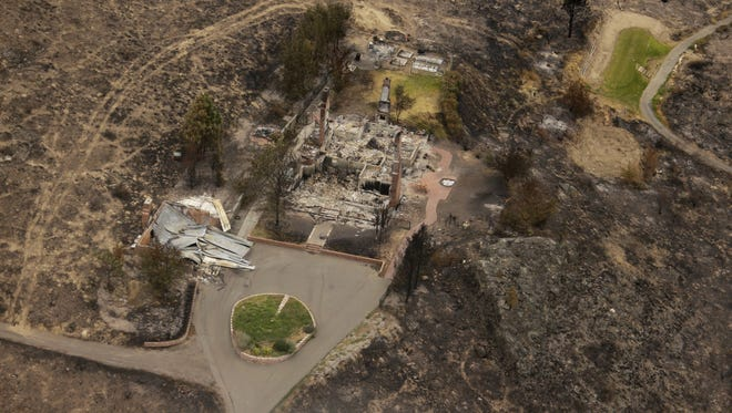 This aerial photo shows structures which were destroyed by wildfires near Pateros, Wash. on Thursday, July 24, 2014. Fire spokesman Pete Buist says the biggest wildfire in the state's history remains at 52 percent contained on Thursday. However, the weather forecast calls for hot and dry conditions to return over the next few days.