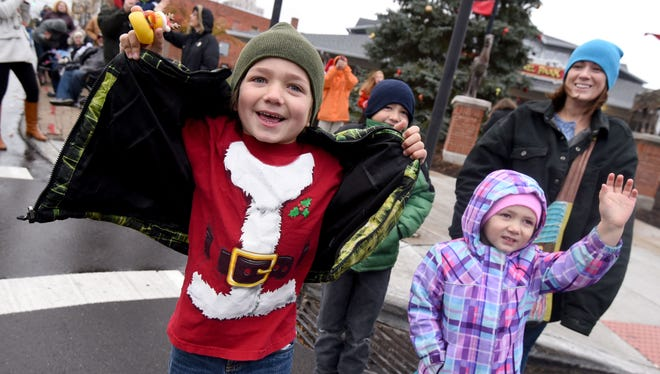 Luca and Adylina Troiano of Crestline try to get Santa's attention during the Holiday Parade on Saturday.