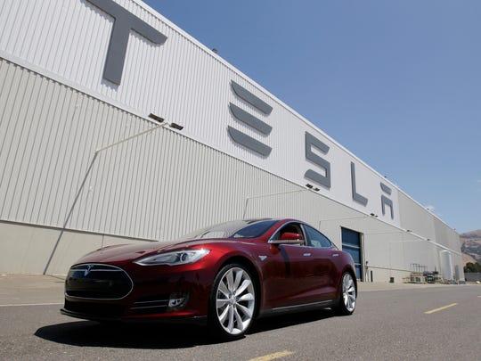 A Tesla Model S driving outside the Tesla factory in