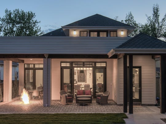 This covered backyard dining room in Old Town Fort Collins has a seating area, a fire feature and paver patio.