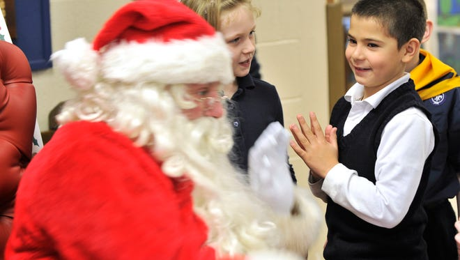 Lukas Edwards eyes up Santa Wednesday, Dec. 17 at St. Mary's Catholic School in St. Clair.