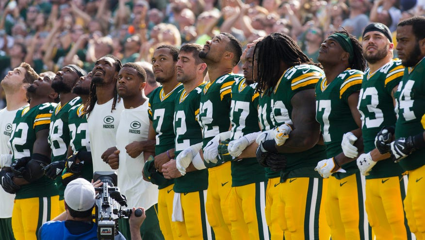 The Green Bay Packers stand and lock arms for the National Anthem prior to  the game against th… af2903fe8