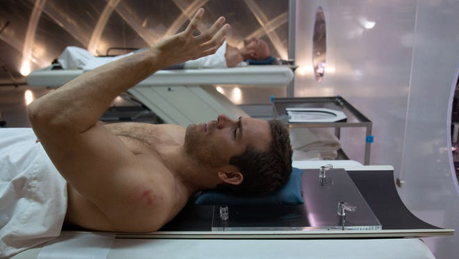 "Damian Hale (Ryan Reynolds) checks out his new body after ""shedding"" his old one (Ben Kingsley, background) in 'Self/less.'"