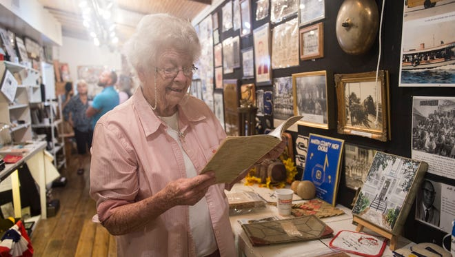 """Winifred Thompson, 89, of Stuart, looks through an old Stuart High School yearbook Oct. 4, 2017, at the Stuart Heritage Museum. Thompson graduated high school in 1945, just after the end of World War II, with less than 50 students in her senior class. """"Everything's changed so completely,"""" Thompson said."""