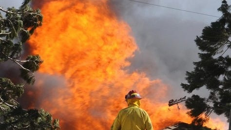 A firefighter approaches a burning house on Windy Hill Way Friday Nov. 18, 2011.