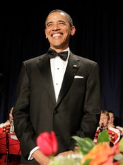 President Barack Obama smiles as he arrives with first lady Michelle Obama at the White House Correspondents Association dinner in Washington on April 30, 2011.