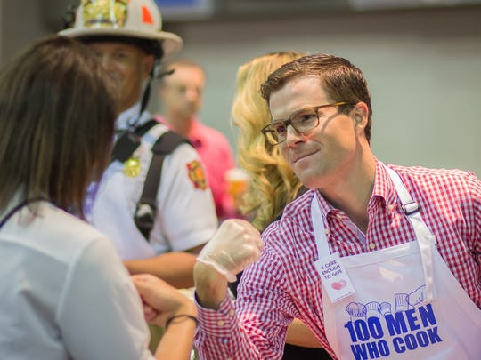 Kyle Fields, general manager for the Indiana office of SS&C Technologies, fist-bumps a fan of his cooking at the 100 Men Who Cook fundraiser on Aug. 27.