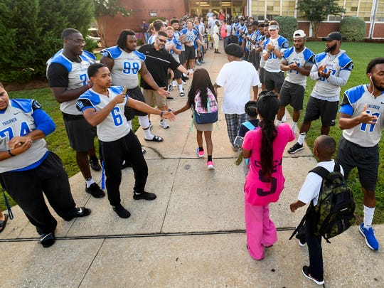 Faulkner University students, athletes, faculty and administration form lines to welcome students at Davis Elementary during the first day of school in Montgomery, Ala. on Thursday August 10, 2017.