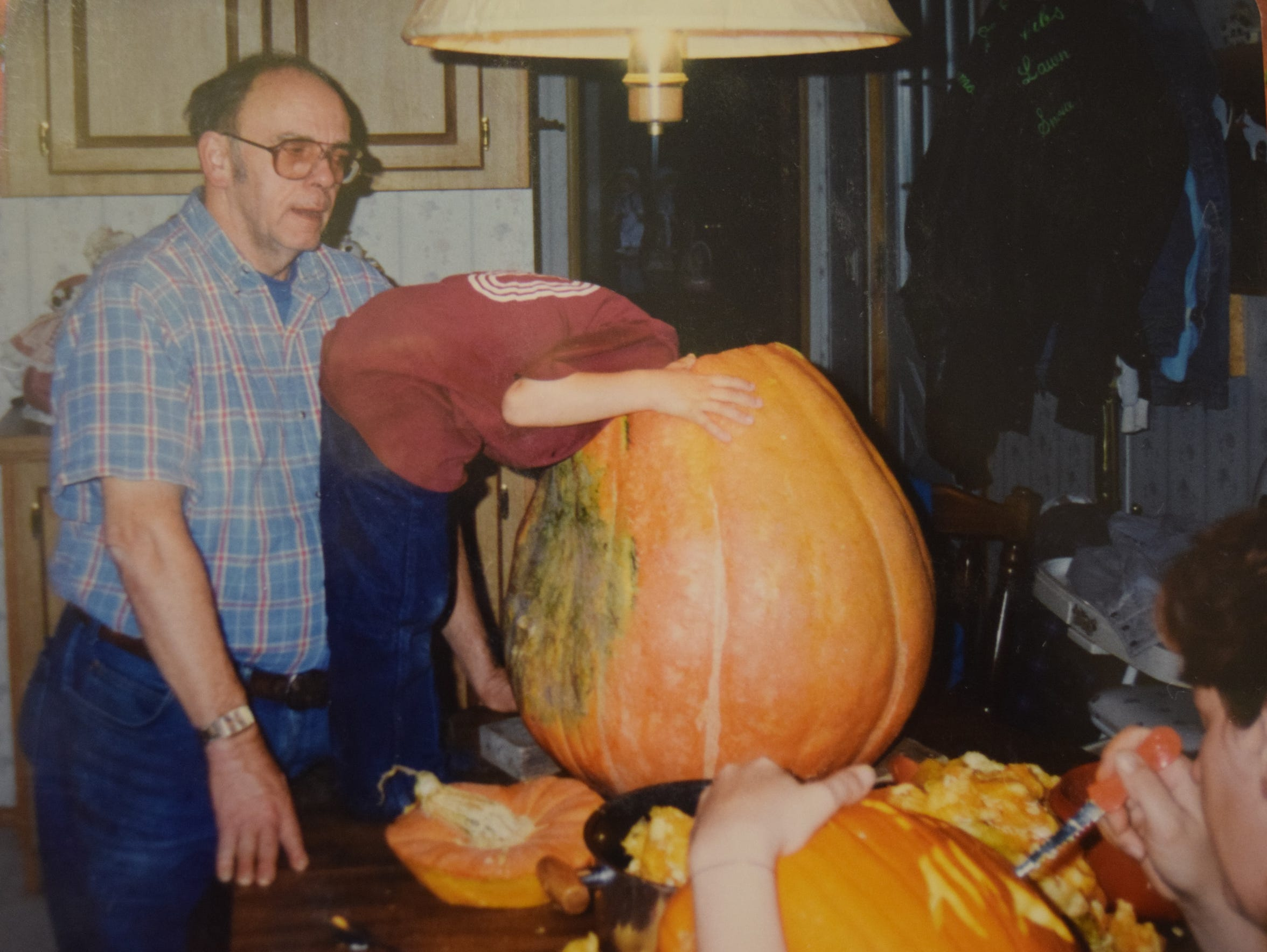 Tysin Gibson with his head in a pumpkin, carving pumpkins