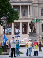 People participate in a peace protest in front of the Capitol on Friday, Sept. 2, 2016. A handful of Lansing residents have been in front of the Capitol every Friday since the Friday after Sept. 11, 2001 to protest in favor of peace.