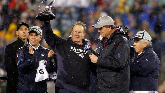 Patriots head coach Bill Belichick celebrates with the Lamar Kraft Trophy while being interviewed by CBS announcer Jim Nantz after the Sunday's win.