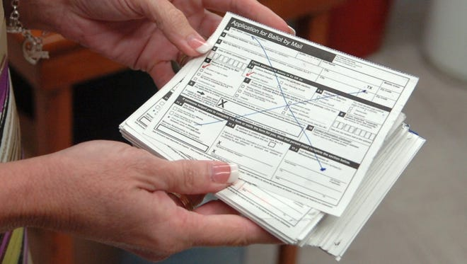 A woman holds a mailed ballot.