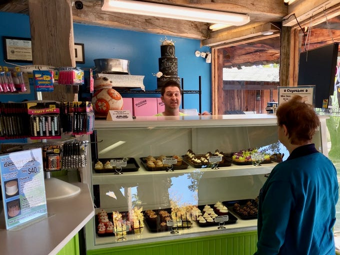A customer orders cupcakes at Sublime Cake & Design