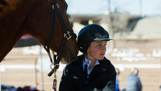 """Erica Rosinski, stands with """"Leo"""" one of the horses at the equestrian stables during a meet Feburary 24, 2017. The New Mexico State University's Equestrian team held its final meet Saturday March 4, 2017, The meet was not only the last of the season but their final home meet as an officially sanctioned NMSU team sport."""