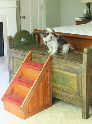 Sparky enjoys the custom stairs, handcrafted by Heather Patchett, that make it easier to get up to his owners' bed.