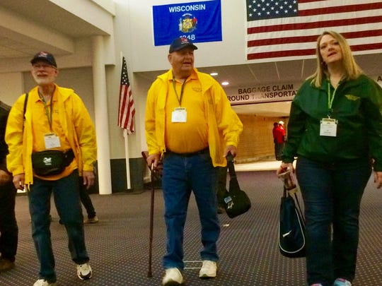 Vietnam veterans Jon Puerner of Weston and Jim Engelson of Mosinee walk with guardian (and Engelson's daughter) Jill Bertolotti of Mosinee at Central Wisconsin Airport Monday as part of a Never Forgotten Honor Flight.