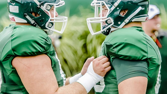 MSU offensive lineman Jack Allen, left, prepares for a blocking drill with his brother, Brian Allen, during a summer camp practice on August 6, 2014.