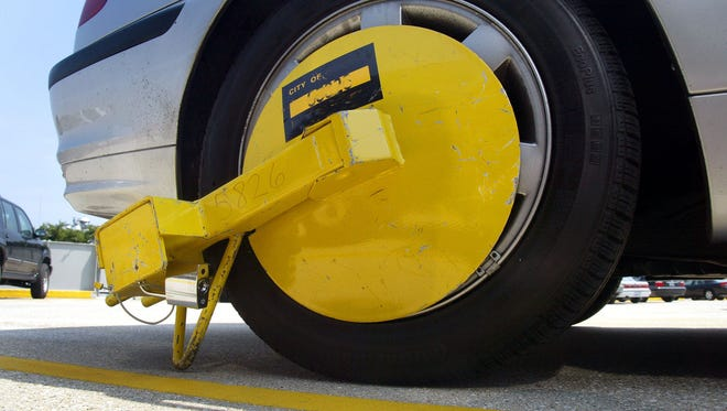 This is a photo illustration of a wheel lock attached to a car.