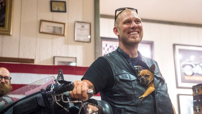 Adam Sandoval takes questions from a crowd in Gettysburg, Pa., about his two-year motorcycle journey with his Chihuahua, Scooter, at Battlefield Harley-Davidson on Oct. 2.