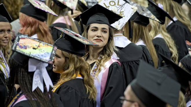 The forty-sixth annual commencement exercises took place on Sunday, May 6, 2018 at the BB&T Arena on the NKU Campus in Highland Heights for their College of Health Professions, Haile/US Bank College of Business and College of Informatics. A graduate searches the stands for her family.
