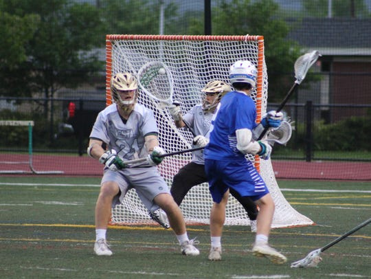 Vestal goalie Luke Barney makes a save as teammate