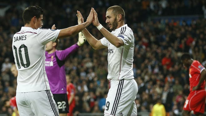 Real Madrid's Karim Benzema celebrates with James Rodriguez after scoring the opening goal during a Group B Champions League soccer match between Real Madrid and Liverpool at the Santiago Bernabeu stadium in Madrid, Spain.